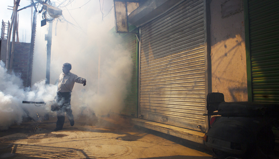 man fumigates an alley to prevent mosquito borne illnesses