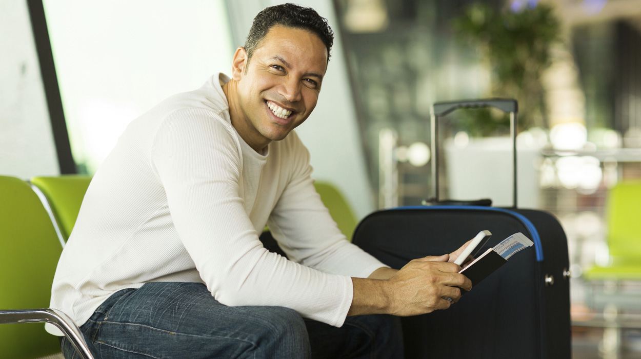male traveler in airport with passport