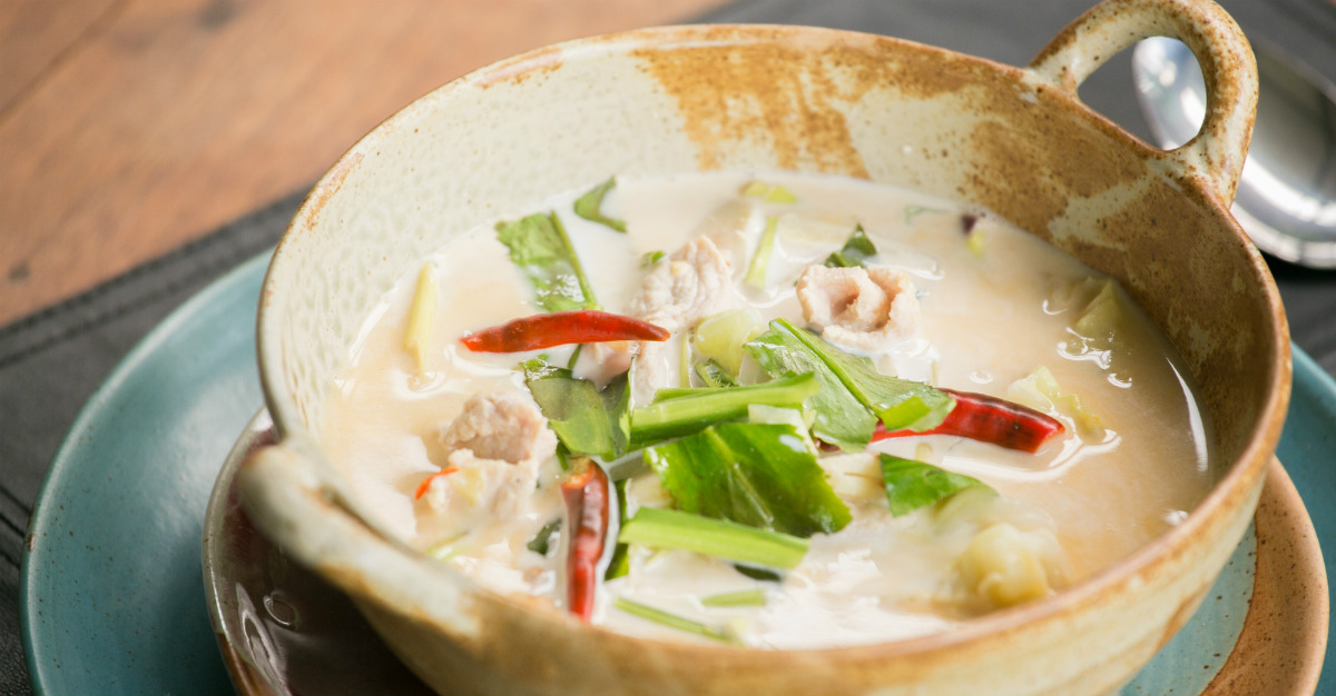 The soup uses chili peppers, but is much less spicy than tom yum.