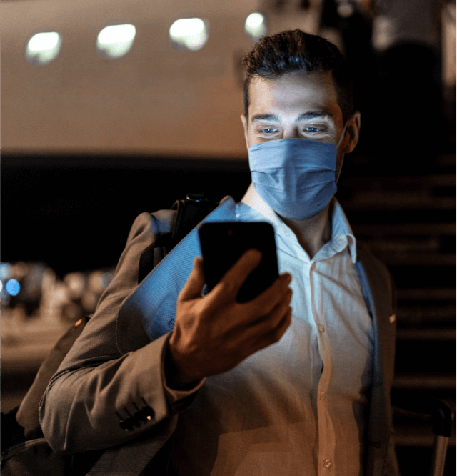 traveler with mask checking phone